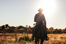 Anonymous Man Riding Horse On Path At Sunset