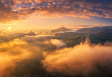 Mountains In Low Clouds At Sunrise In Summer. Aerial View Of Mountain Peak In Fog. Beautiful Landscape With High Rocks, Forest, Colorful Sky. View From Above Of Mountain Valley In Clouds. Foggy Hills