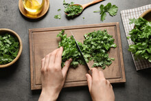 Woman Cutting Fresh Green Cilantro At Grey Table, Top View