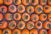 Delicious Ripe Persimmon Fruits Close-up On The Market Stall