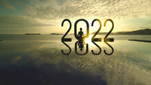 Woman Exercising Yoga With 2022 Numbers At Sunset