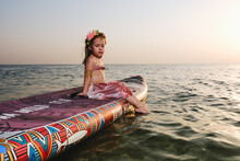 Little Girl On A Surfboard In The Sea At Sunset. In Moana's Cast.