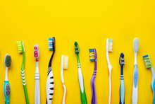 Toothbrushes On Yellow Background. Hygiene Of The Oral Cavity.