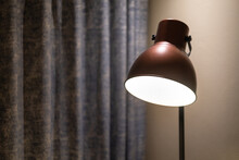 A Classic Style Lighting Lamp During Turning-on The Light With Blurred Background Of Blue Curtain And Wall In Living Room. Interior Decoration Object Photo. Selective Focus At The Lamp Part.