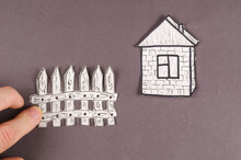 Hand Spreads The Applique On A Gray Background. Minimalist Composition With Drawn House And Stackable Fence On Gray Background. Hand-drawn Of Wooden Fence And Stone House On White Paper. Top View.