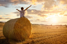 Boy Sitting On A Hay Bale With Arms Raised In Summer Watching The Sunset
