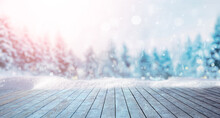 Winter Festive Christmas Background - Surface Of Wooden Planks With Snow Cap On Light Blurred Background Of Snow-covered Forest And Falling Light Flakes Of Snow.