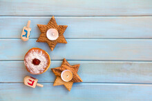 Wooden Candlesticks In The Shape Of Star, Donut And Dreidels On Background Of Blue Painted Wooden Planks With Space For Text. Jewish Holiday Hanukkah. Top View, Flat Lay