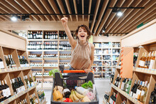 Young Smiling Woman In Casual Clothes Mask Shopping At Supermaket Store With Grocery Cart Choose Alcohol Wine Bottle Do Winner Gesture Clench Fist Inside Hypermarket. Purchasing Gastronomy Concept