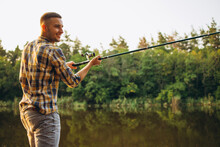 Portrait Of Young Smiling Man Standing On Pier And Fishing On Warm Summer Evening. Hobby