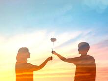 花を持つ男女のシルエット_夕焼け背景