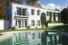 Large House With Swimming Pool And Trees In Sunny Garden