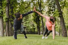 Fit Healthy Young Male And Female Athletes Boyfriend And Girlfriend Friends Couple Standing In Plank Position Stretching Warming-up Before Training Workout Together Outdoors In City Park.