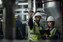 Male Engineer Training A Female Engineer In An Industrial Plant Room