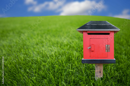 Fototapeta A red wooden postbox lay on the green grass and blurred sky.