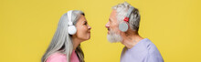 Side View Of Funny Multiethnic And Middle Aged Couple In Wireless Headphones Looking At Each Other Isolated On Yellow, Banner