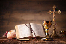 Catholic Religion Concept. Catholic Symbols Composition. The Cross, Holy Bible, Rosary And Golden Chalice On The Altar.
