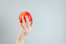 Red Apple In Female Hand Isolated On Grey Wall Background. Apple Vitamin Snack. Healthy Nutrition Diet.