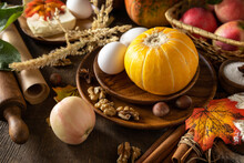 Seasonal Food Autumn Baking Background - Ingredients For Baking (pumpkin, Apples, Eggs, Flour, Sugar And Spices) On A Wooden Table.