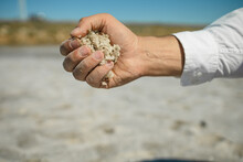 Hands Holding Sea Salt Deposits On Shores Of Beautiful Pink Lake