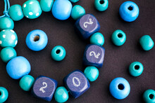 A Bacelet Of Wooden Beads With Numbers 2022 On Black Background.
