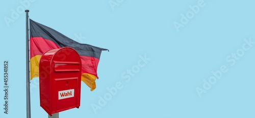 Obraz na plátně Banner with big red modern metal postbox with note written in German Wahl meaning Vote and standing behind German national flag at blue sky solid background with copy space