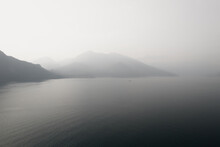 Black And White Photo With A Foggy Mountains In Como Lake. Hazy And Misty Lake View