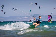 Smiling Woman Kitesurfing In Ocean With Other Kitesurfer, Tarifa Beach, Cadiz, Andalusia, Spain
