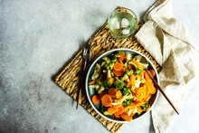 Overhead View Of A Bowl Of Beans, Carrots, Broccoli And Cauliflower With A Glass Of Ice Water