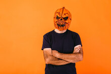 Man Wearing Scary Pumpkin Latex Mask With Blue T-shirt With Crossed Arms, On Orange Background. Halloween And Days Of The Dead Concept.