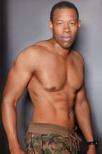 Portrait Of Shirtless, Muscular Black Man Standing In Front Of Gray Wall