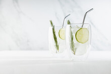 Refreshing  Mojito Cocktail With Ice Cubes, Lime Slices, Sliver Straws, Green Rosemary Twig In Two Mugs In Elegant Modern White Interior On Soft Light Wood Table.