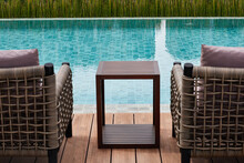 Blur Table And Chairs  In Front Of Blue Water Swimming Pool.   Blur Table And Chairs In Foreground View Of Swimming Pool.