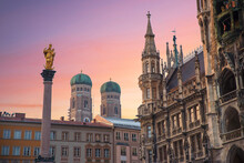 The Marian Column, Town Hall Building And Towers Of Frauenkirche, Historic Architecture Munich Marienplatz. At Sunset