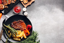 Plates With Tasty Pork Steaks And Grilled Vegetables On Grey Background