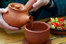 Pour Tea Into A Clay Cup From A Clay National Georgian Teapot