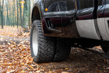 Close-up Detail Bottom Pov View Of Dual Twin Offroad Performance Wheel Of Super Heavy Duty Pickup Truck Car At Autumn Forest Countryside Driveway. Autumn Weather Woods Offroad Vehicle Drive