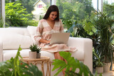 Beautiful woman using laptop on sofa in living room decorated with houseplants. Interior design