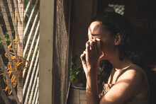 A Young Woman Sobs Uncontrollably After Being Informed Of A Loved One's Passing. Dramatic Indoor Scene By The Window.