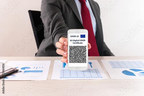 Businessman showing his european covid vaccine certificate