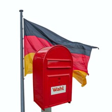 Big Red Modern Metal Postbox With Note Written In German Wahl Meaning Vote And Standing Near German National Flag Isolated At White Background. Concept Voting In Germany.