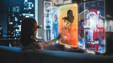 Beautiful Young Woman Is Sitting On A Couch At Night At Home, Wearing VR Headset And Choosing A Movie To Watch On A Futuristic Augmented Reality Hologram Screen. Futuristic AR Or VR Concept.