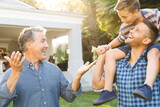 Portrait of smiling caucasian grandfather and adult son with grandson on his shoulders in garden