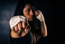 Young Latin Woman Practicing Boxing And Kickboxing. She Scores A Direct Punch With Her Fist. Differential Focus. Sport, Fitness, Training Concept.
