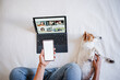 top view of unrecognizable woman at home doing video call with friends on mobile phone while cute jack russell dog resting on bed. Home office, Pets, love and relax