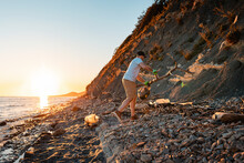 World Environment Day. A Male Activist Is Cleaning Up On A Wild Beach. In The Background, The Sea And The Sunset. The Concept Of Cleaning The Coastal Zone