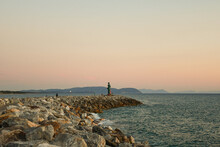 Seascape From The Rocky Walkway Of The Harbor With The Tuscan Coastline In The Background At Sunset, San Vincenzo, Livorno, Tuscany, Italy