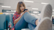Happy Asian Woman Using And Checking Her Smartphone While Sitting On Chair In Terminal Hall While Waiting Her Flight At The Departure Gate In International Airport. Women Happy In Airport Concept.