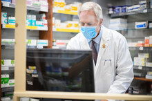 Pharmacist At Work With A Computer In His Store