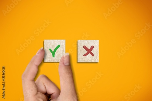 Right and wrong icons on wooden cubes with hand choosing the right icon